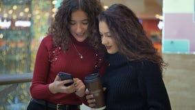 Duas meninas bonitos estão considerando algo no telefone filme
