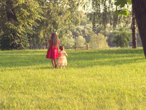 Duas meninas bonitos nos vestidos bonitos que têm o divertimento no por do sol toned fotos de stock