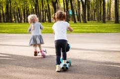 Duas meninas bonitos pequenas montam seus 'trotinette's Imagem de Stock Royalty Free