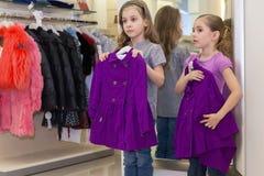 Duas meninas bonitos pequenas perto de um espelho tentam sobre a roupa imagem de stock