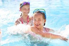 Duas meninas bonitos que jogam na piscina Fotos de Stock