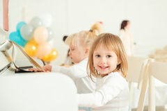 Duas meninas bonitos que jogam o piano em um estúdio fotos de stock