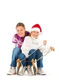 Duas meninas bonitos que montam em um pequeno trenó Imagens de Stock Royalty Free