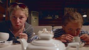 Duas meninas caucasianos novas bebem o chá e o gracejo no café na noite após uma caminhada video estoque