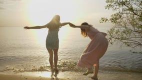 Duas meninas caucasianos novas nos vestidos estão correndo ao longo da areia no mar, rir, abraçando, natureza no fundo video estoque