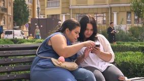 Duas meninas caucasianos obesos que olham o smartphone e que typying junto ao sentar-se exterior no banco filme