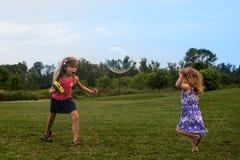 Duas meninas caucasianos pequenas que jogam com bolhas e para ter o divertimento no campo no verão fotos de stock