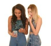 Duas meninas chocadas pela mensagem de telefone imagens de stock royalty free