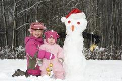 Duas meninas com bonecos de neve fotos de stock royalty free