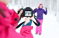 Duas meninas com a câmera que toma imagens na neve no inverno Foto de Stock Royalty Free