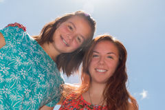 Duas meninas com céu azul e luz solar no fundo Fotos de Stock Royalty Free