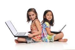 Duas meninas com computadores portáteis Foto de Stock Royalty Free
