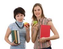 Duas meninas com maçãs e livros; isolado no branco Imagens de Stock