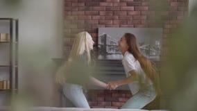 Duas meninas com o cabelo louro e escuro que salta guardando as mãos na sala de visitas Menina moreno e menina do albino com filme
