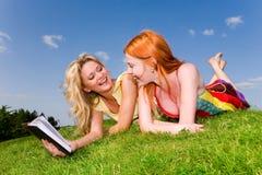 Duas meninas com o caderno na grama verde Foto de Stock Royalty Free