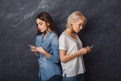 Duas meninas com os smartphones que olham nos smartphones Fotos de Stock Royalty Free