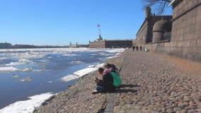 Duas meninas com os telefones que sentam-se na fortaleza de Peter e de Paul St Petersburg filme