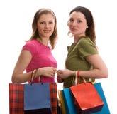 Duas meninas com sacos de compra. Isolado no branco. Fotografia de Stock Royalty Free