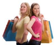 Duas meninas com sacos de compra. Isolado no branco. Foto de Stock