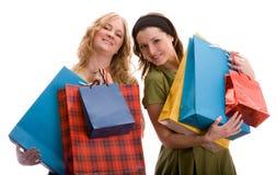 Duas meninas com sacos de compra. Isolado no branco. Fotografia de Stock