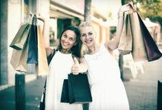 Duas meninas com sacos de compras fora Imagens de Stock