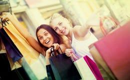 Duas meninas com sacos de compras fora Imagem de Stock
