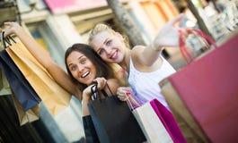 Duas meninas com sacos de compras fora Imagens de Stock Royalty Free