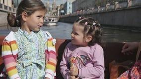 Duas meninas com seus pais em um barco de turista ao longo dos rios video estoque