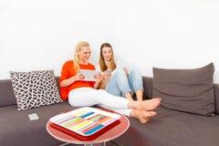 Duas meninas com tabuleta e o telefone esperto Imagens de Stock