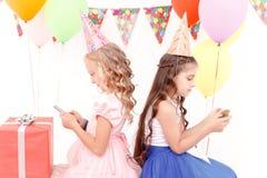 Duas meninas com telefone celular durante a festa de anos imagem de stock