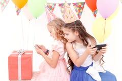 Duas meninas com telefone celular durante a festa de anos imagem de stock royalty free