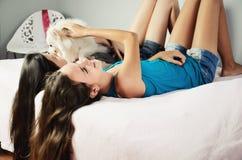 Duas meninas com um Pomeranian colocam na cama e no riso horizonte Fotografia de Stock