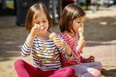 Duas meninas comem o gelado ao sentar-se no campo de jogos imagens de stock royalty free
