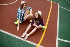 Duas meninas consideravelmente louras que vestem camisas quadriculados, tampões e short da sarja de Nimes estão sentando-se nos l imagens de stock royalty free