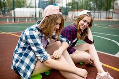 Duas meninas consideravelmente louras que vestem camisas quadriculados, tampões e short da sarja de Nimes estão sentando-se nos l fotos de stock