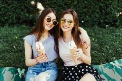 Duas meninas consideravelmente morenos que falam e que comem o gelado exterior na grama imagem de stock royalty free