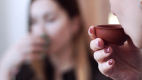 Duas meninas da aparência caucasiano para sentar e apreciar o chá delicioso dos copos pequenos Cerimônia de chá, close-up vídeos de arquivo