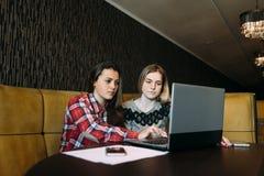Duas meninas da estudante das amigas que olham proximamente na tela do portátil fotos de stock