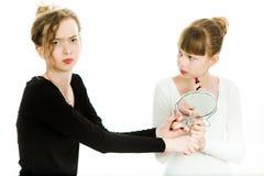 Duas meninas da puberdade em vestidos preto e branco barganham para conseguir um espelho fazer para compor - a rivalidade da irmã foto de stock royalty free