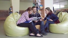 Duas meninas da universidade e um menino que olha através dos livros interessantes filme