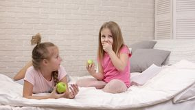 Duas meninas das crian?as pequenas comem ma??s frescas verdes