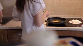 Duas meninas de amor preparam o café da manhã em casa na cozinha, elas fritam ovos na bandeja filme