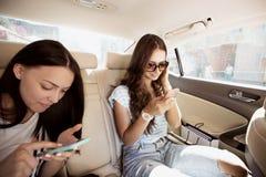 Duas meninas de cabelo escuro bonitas, vestidas no estilo ocasional, estão sentando-se no banco traseiro de uma fantasia e no tex imagem de stock