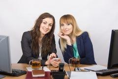 Duas meninas de escritório que conversam e que bebem o chá em sua mesa Foto de Stock Royalty Free