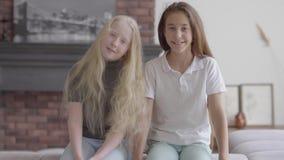 Duas meninas de sorriso bonitos que sentam-se no sofá que ooking na câmera na sala de visitas Conceito da amizade carefree video estoque