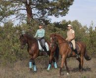 Duas meninas de sorriso montam horseback. Fotos de Stock