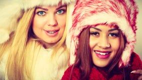 Duas meninas de sorriso na roupa morna do inverno Foto de Stock
