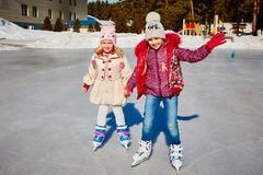 Duas meninas de sorriso pequenas montam no gelo na roupa ocasional brilhante Arrendamento do patim no hotel outdoors foto de stock