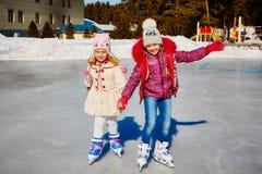 Duas meninas de sorriso pequenas montam no gelo na roupa ocasional brilhante Arrendamento do patim no hotel outdoors fotografia de stock royalty free