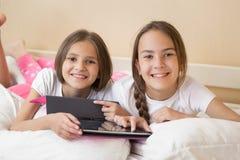 Duas meninas de sorriso que encontram-se na cama e que usam a tabuleta digital Foto de Stock Royalty Free
